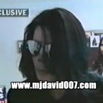 Michael Jackson with sunglasses talking to a report